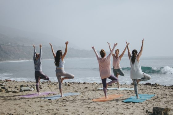 People doing Tree pose on the beach