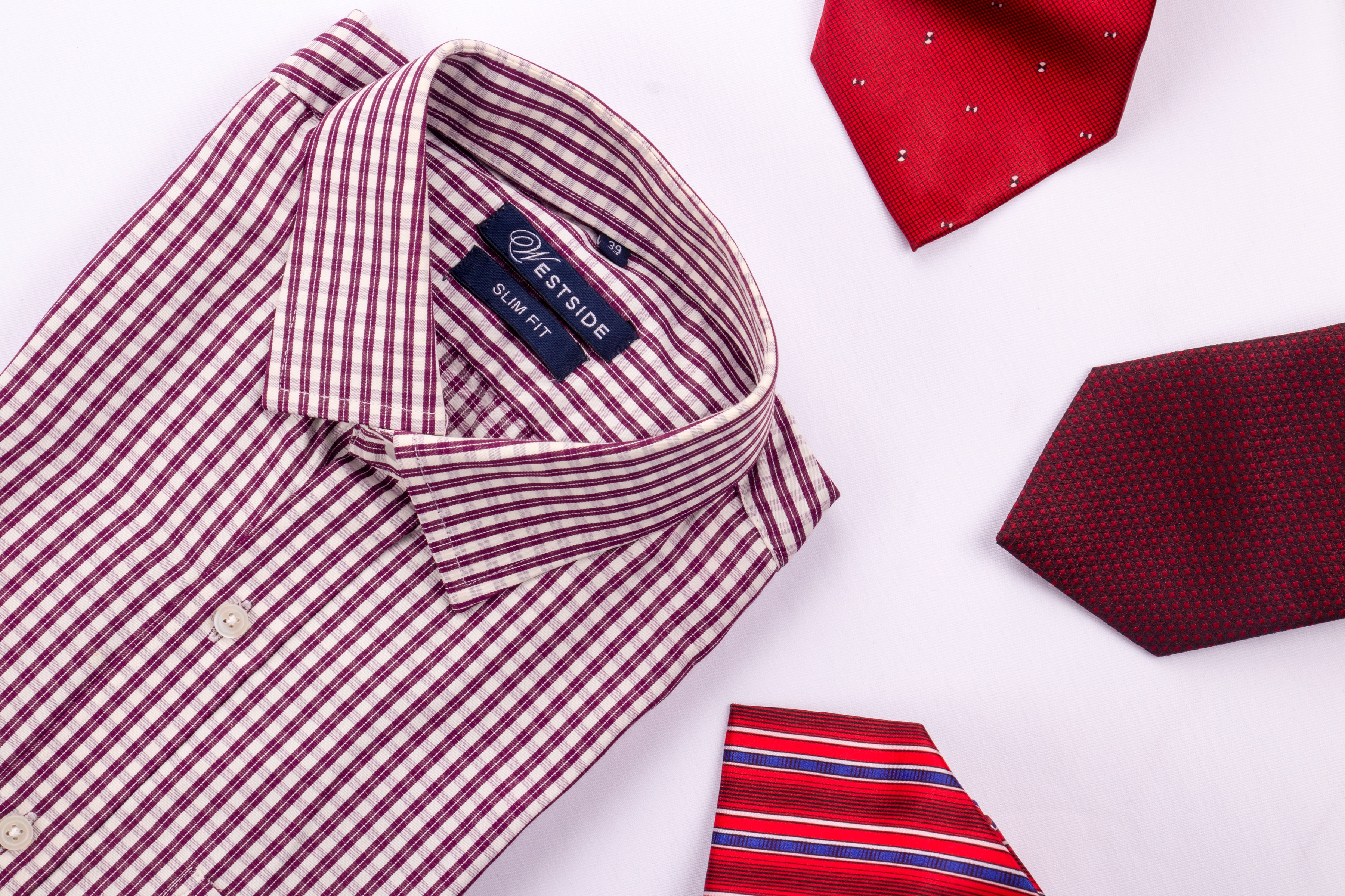 Shirt with three ties beside it